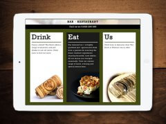 The About Us page from the website viewed on a tablet on a dark wooden background