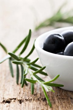 Close-up of black olives in a white bowl with sprig of rosemary
